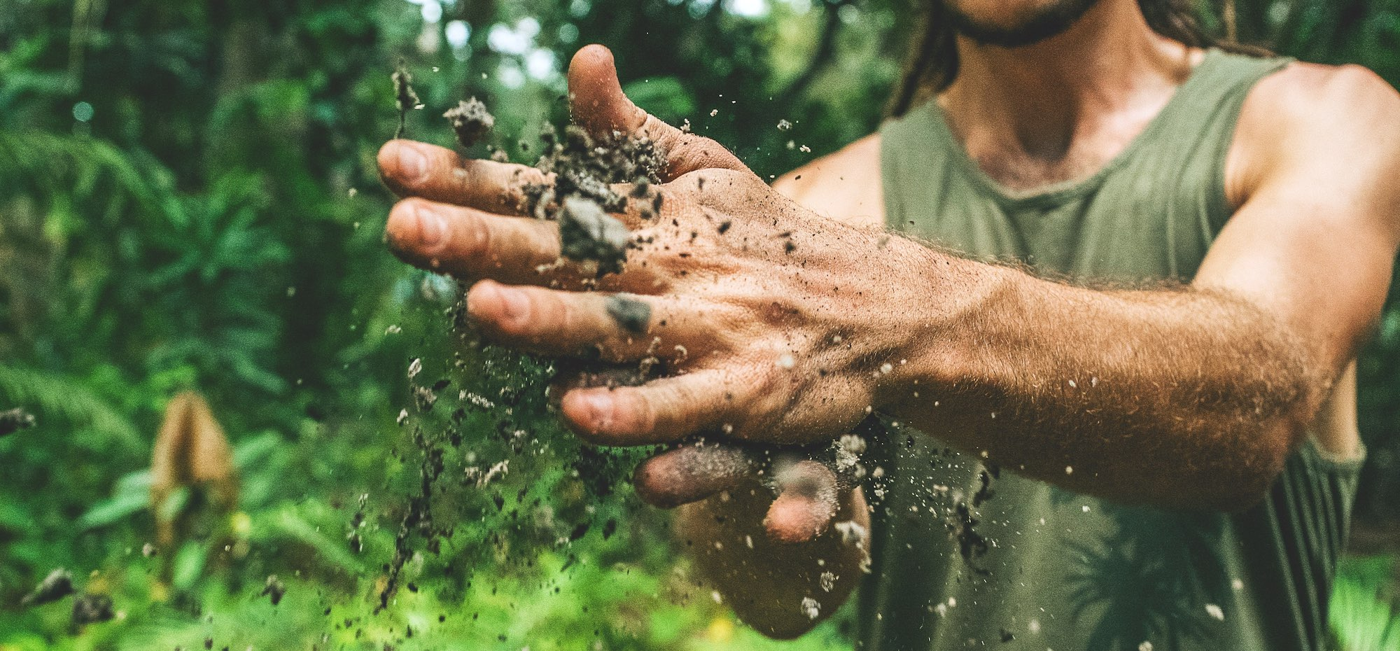 male hands brushing dirt through them