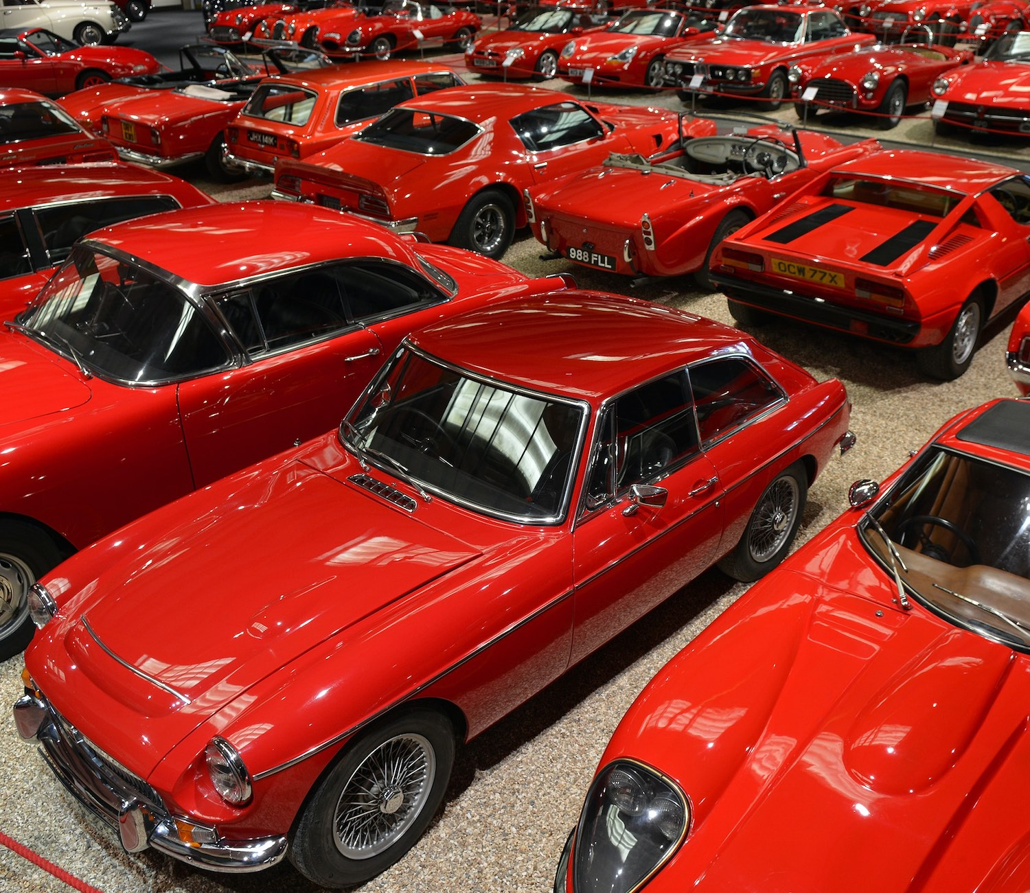 a showroom with lots of red cars in rows