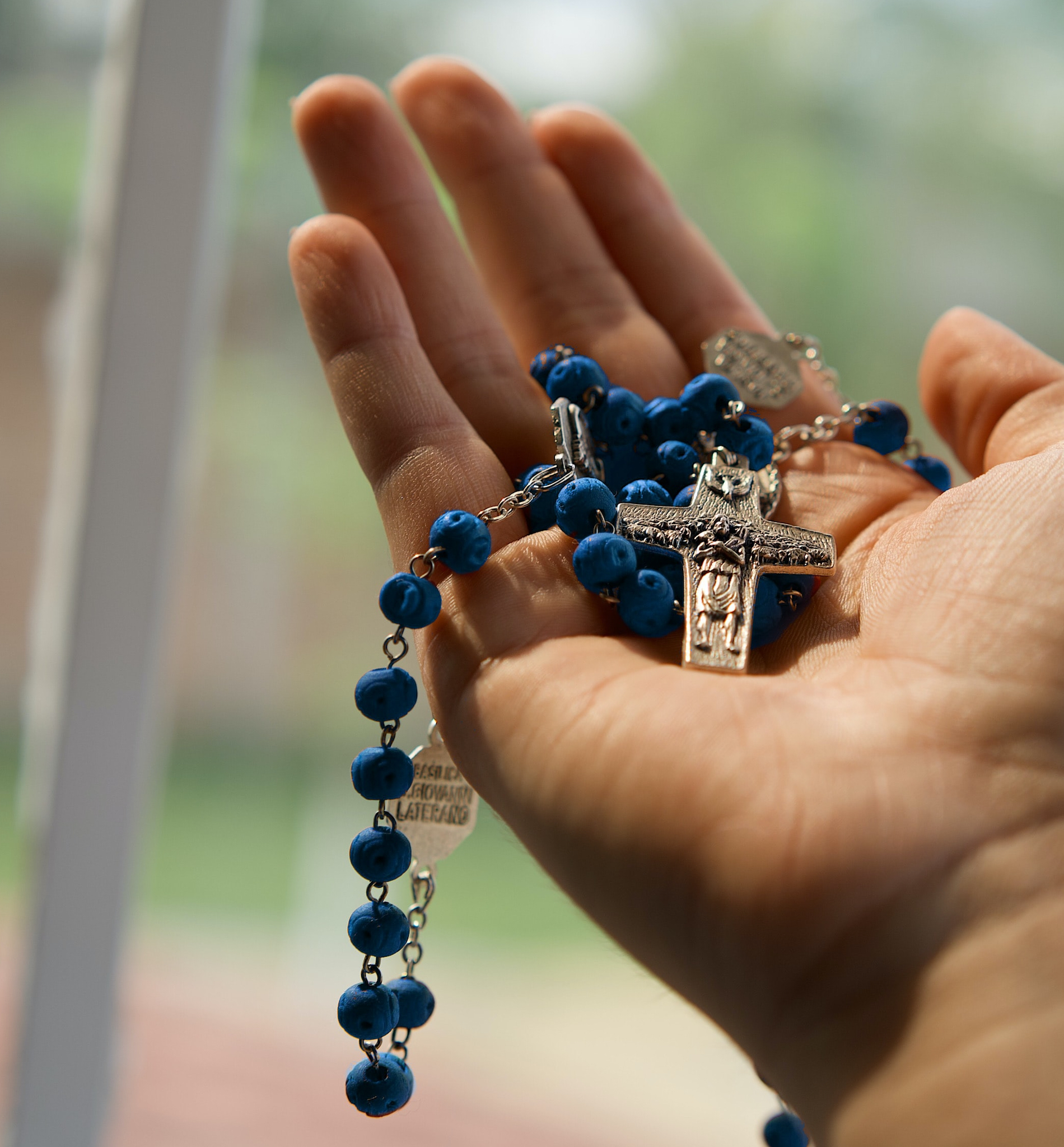 hand holding blue rosary