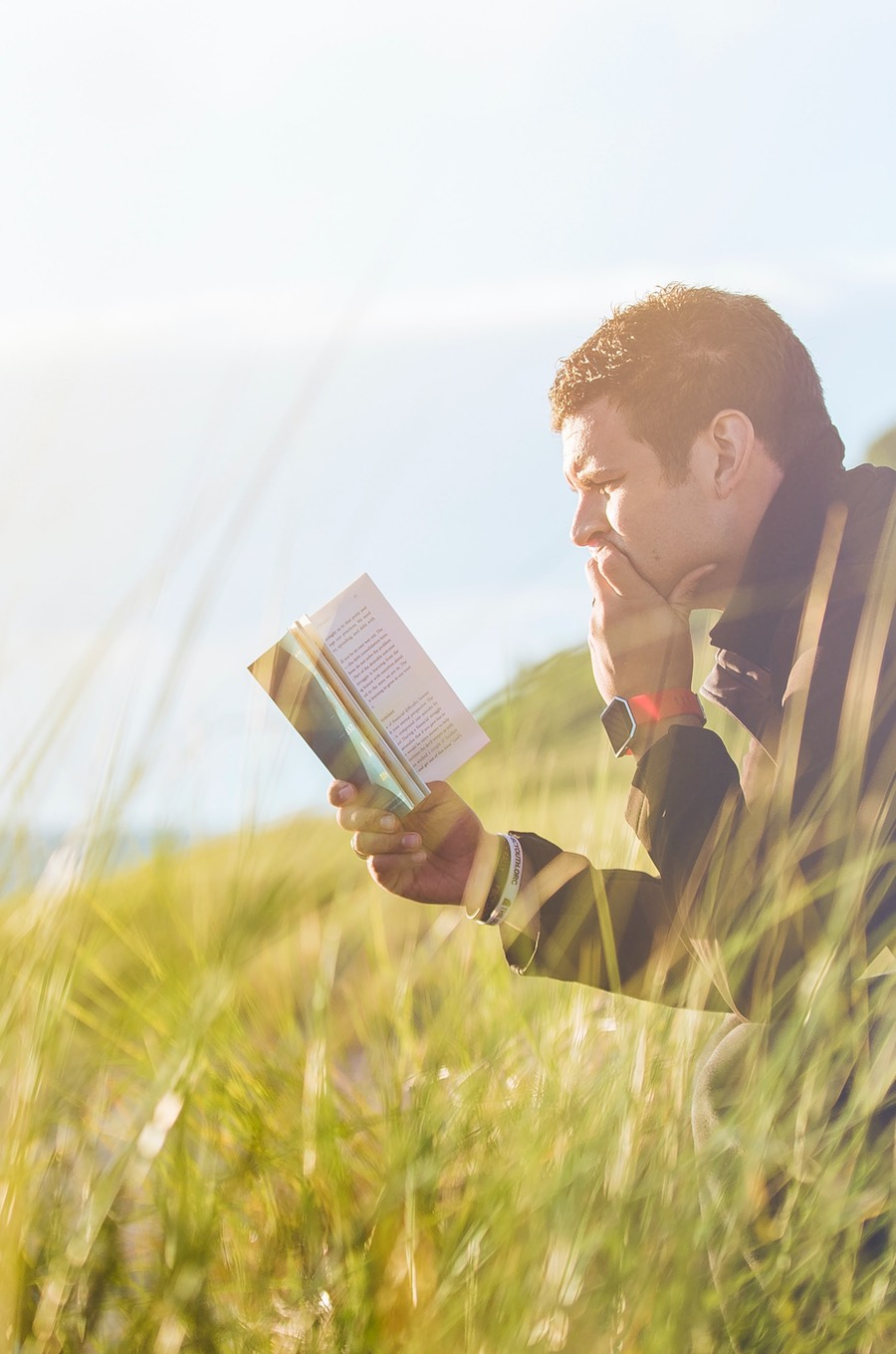 man reading book in a field