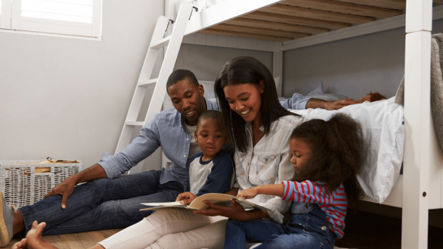 family of two parents and two kids reading a book while leaned up against a bunk bed
