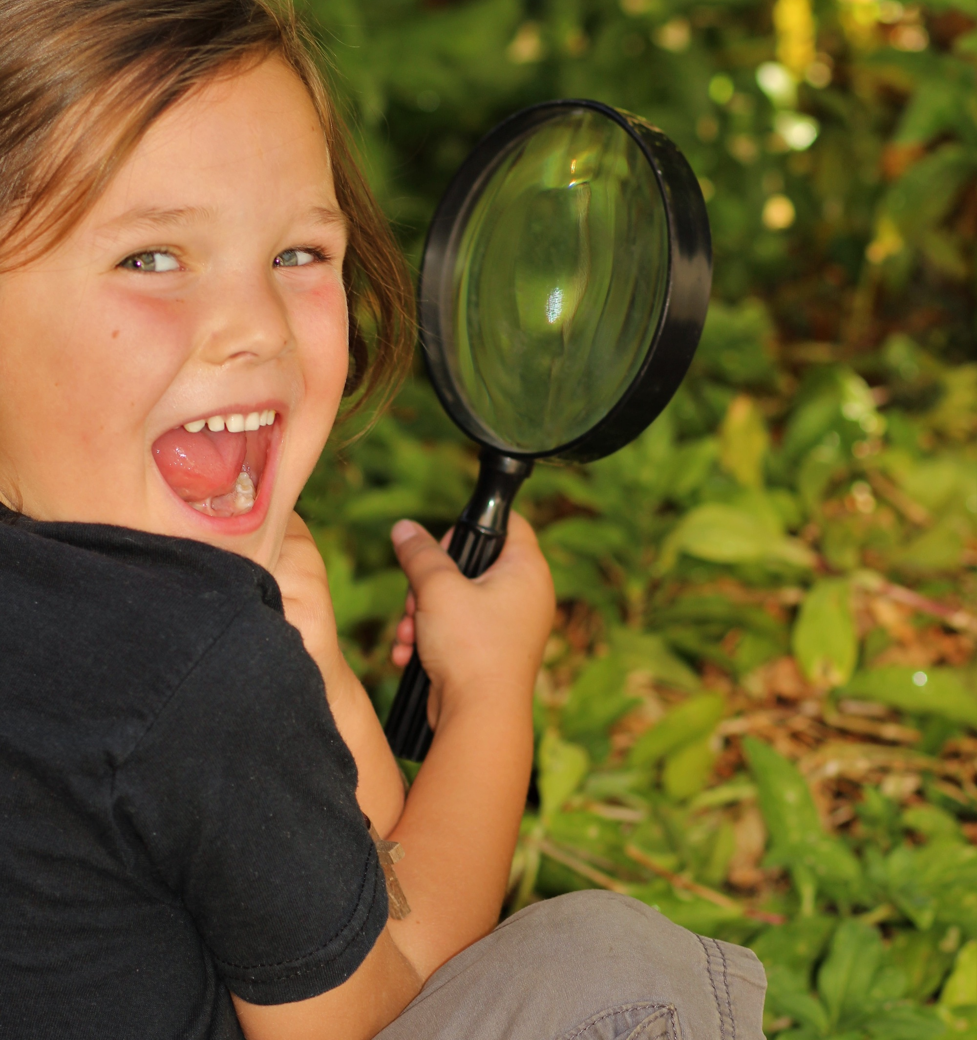 child with magnifying glass crouches outside