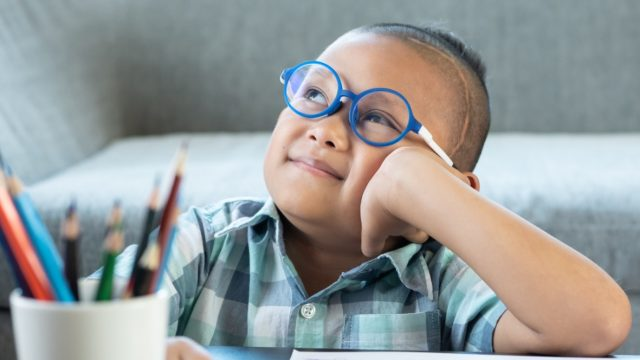 child in glasses looking into space while drawing