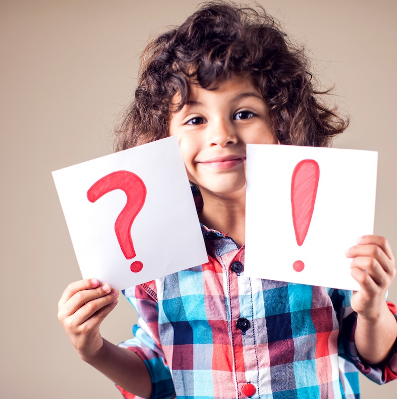 child holding two pieces of paper, one with an exclamation point and the other a question mark on it