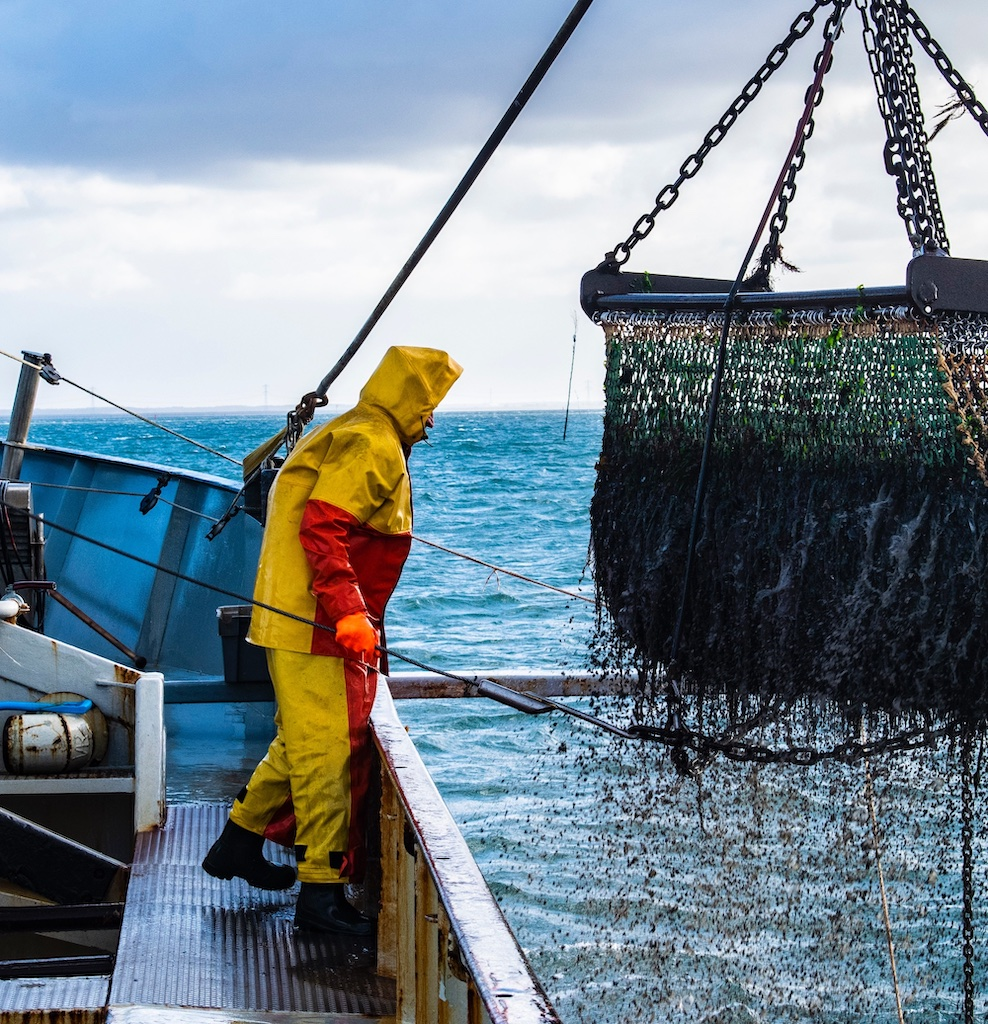 man on a fishing boat standing next to a net that has been drawn up