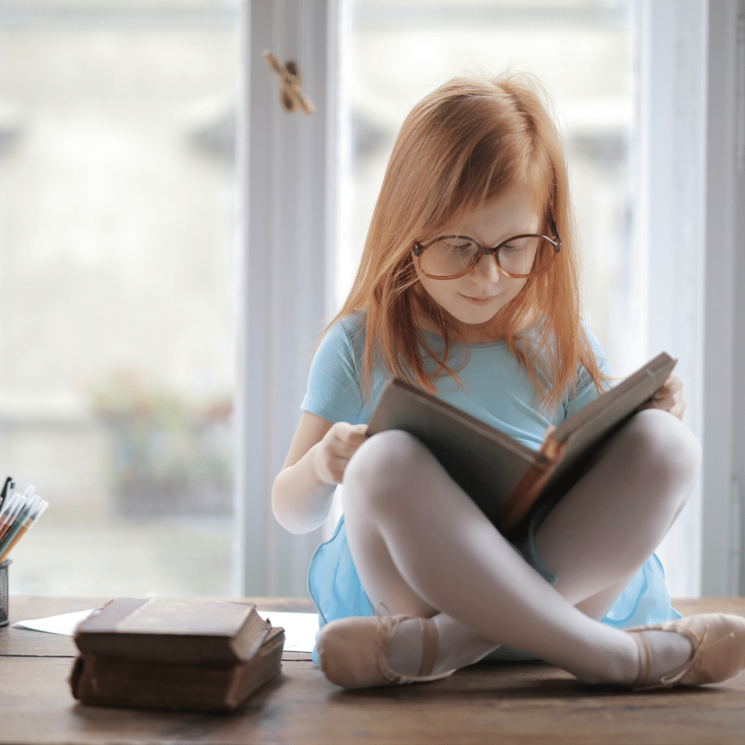 girl reading a book in a windowsill