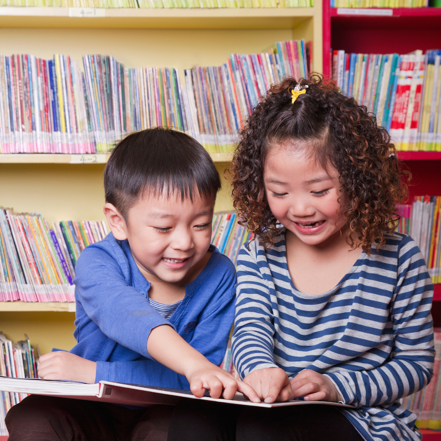 two children looking at a book together