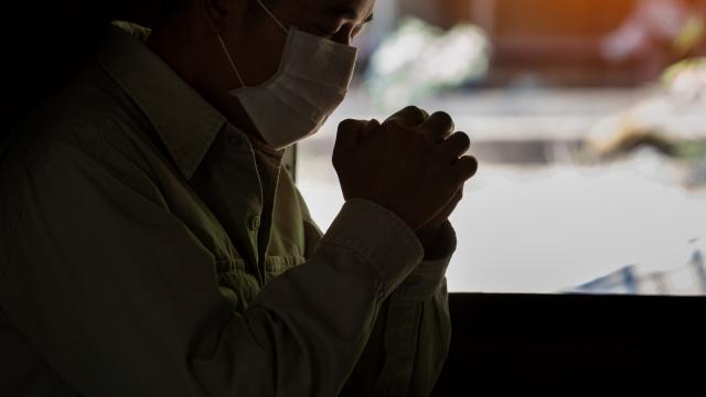Man prays while wearing COVID-19 mask